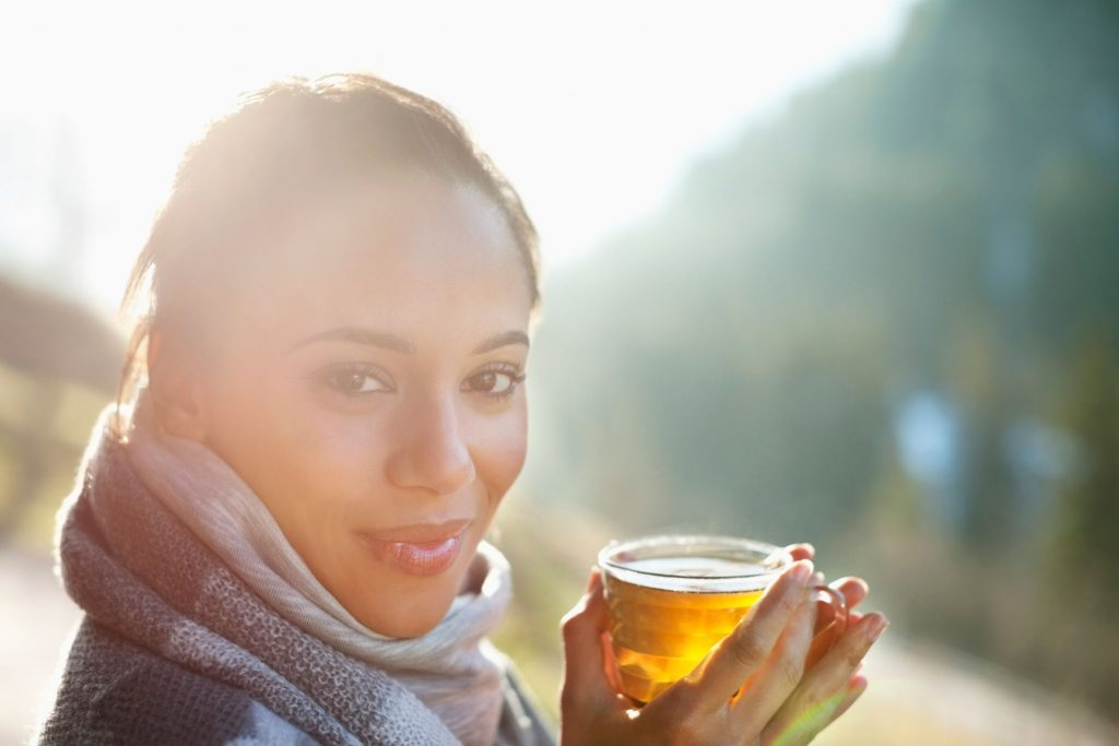 photo of smiling woman in scarf drinking cider