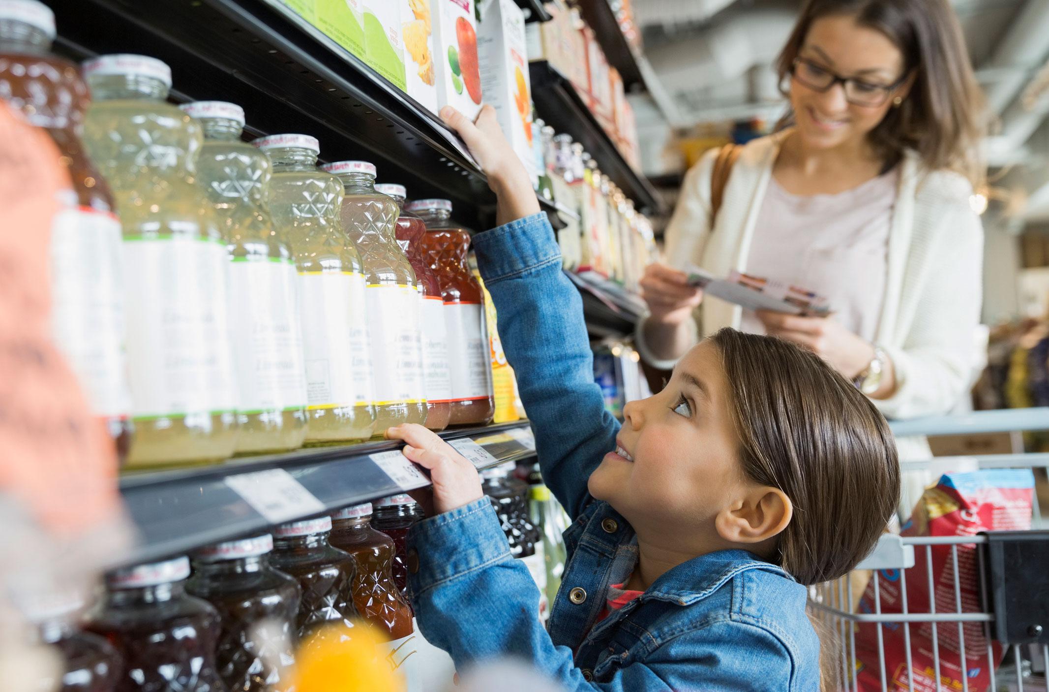 girl reaching for juice on shelf in market