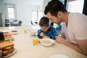 father and son using tablet while eating breakfast