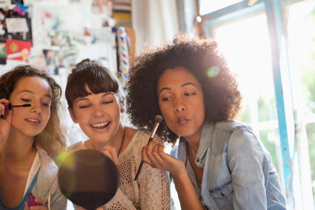 photo of women applying makeup in bedroom